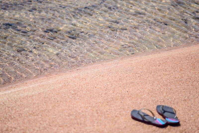 Paar van Flip Flops bij Oever van Sandy Beach stock afbeelding