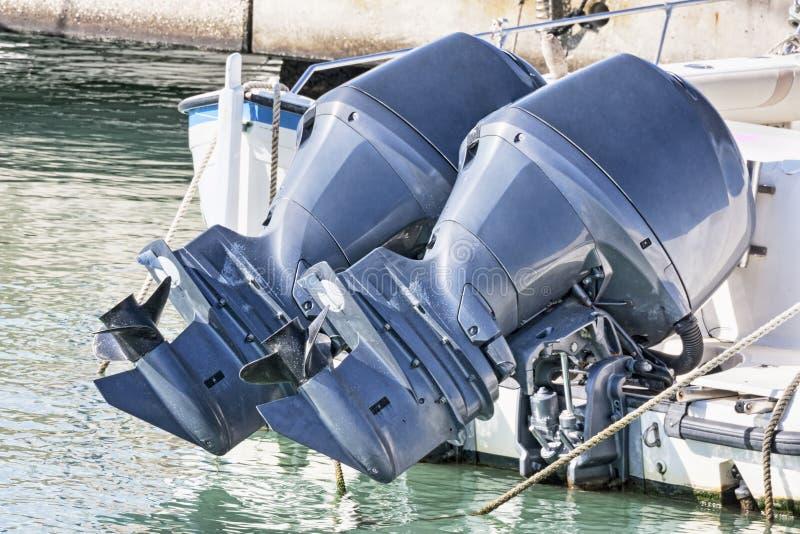 Paar van gebruikte blauwe buitenboordmotoren opgezet op een motorboot stock foto's