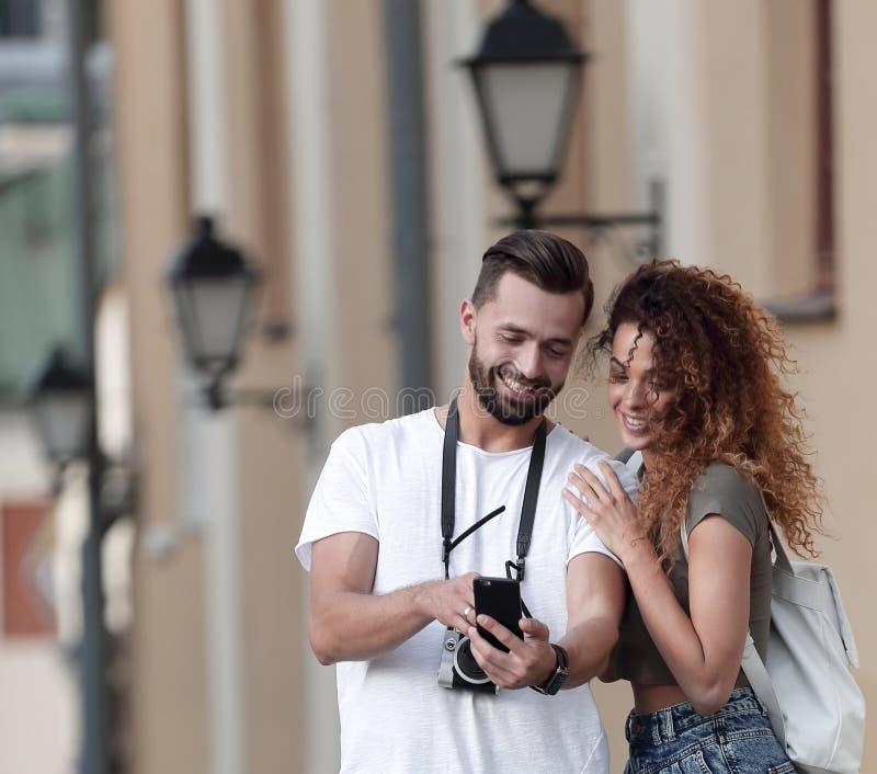 Paar van gelukkige glimlachende toeristen die rond de stad lopen stock foto's
