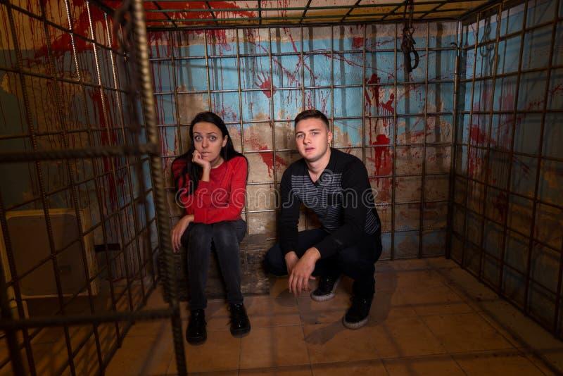 Paar van Halloween-slachtoffers die in een metaalkooi worden gevangengenomen stock afbeelding