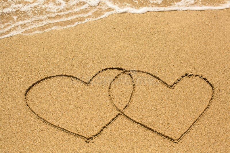 Paar van harten op het strandzand worden getrokken in zonnige dag die Liefde stock fotografie