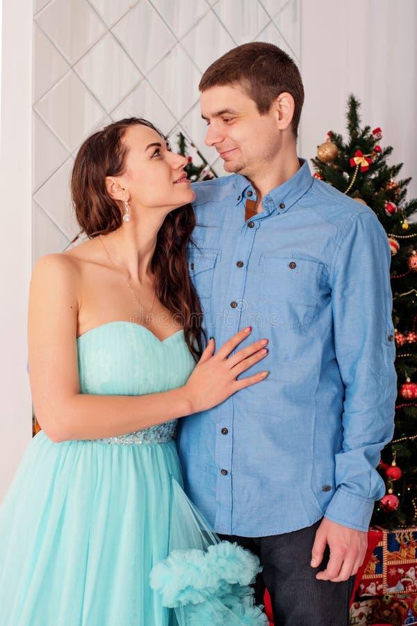 Paar van jonge minnaarsfamilie het staren ogen in de ogen met tederheid op de vooravond van het nieuwe jaar dichtbij de Kerstboom royalty-vrije stock fotografie