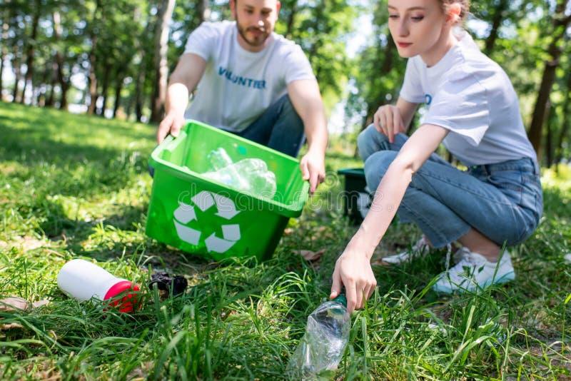 paar van jonge vrijwilligers met recyclingsdoos het schoonmaken royalty-vrije stock foto
