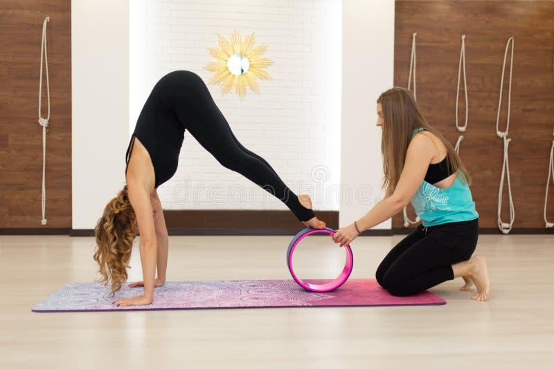 Paar van jonge vrouw in de oefeningen van een sportkledingsyoga met een yogawiel in de gymnastiek Het uitrekken zich en wellnessl stock foto