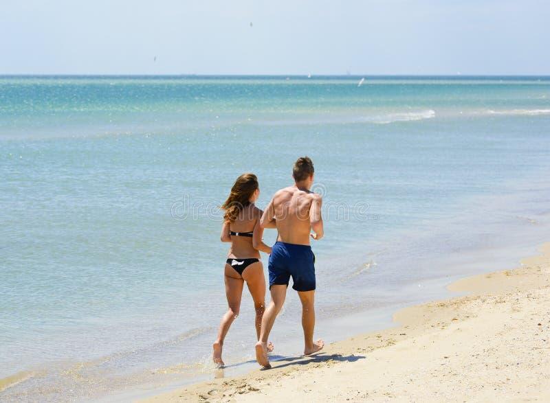 Paar van jongeren die of op het strand lopen aanstoten stock fotografie
