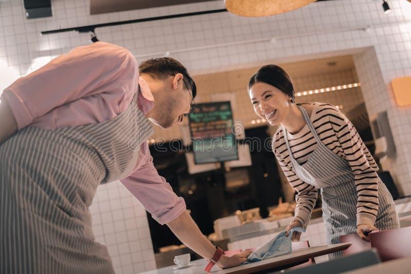 Paar van kelners die terwijl samen het schoonmaken van de lijst lachen royalty-vrije stock foto's