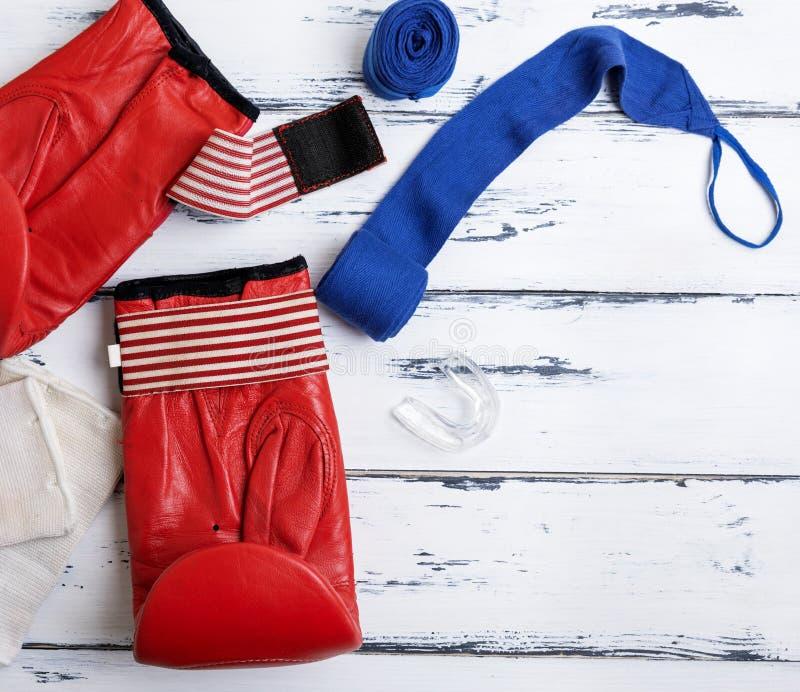 Paar van leer rode bokshandschoenen en blauw verband stock foto's