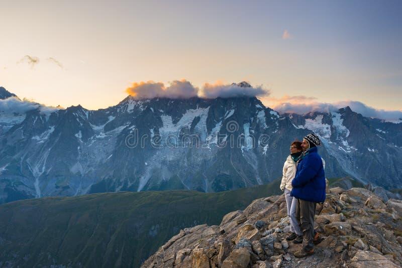 Paar van mensen die de zonsopgang over Mont Blanc-berg piek 4810 m bekijken Valle D ` Aosta, Italiaanse de zomeravonturen en trav stock fotografie