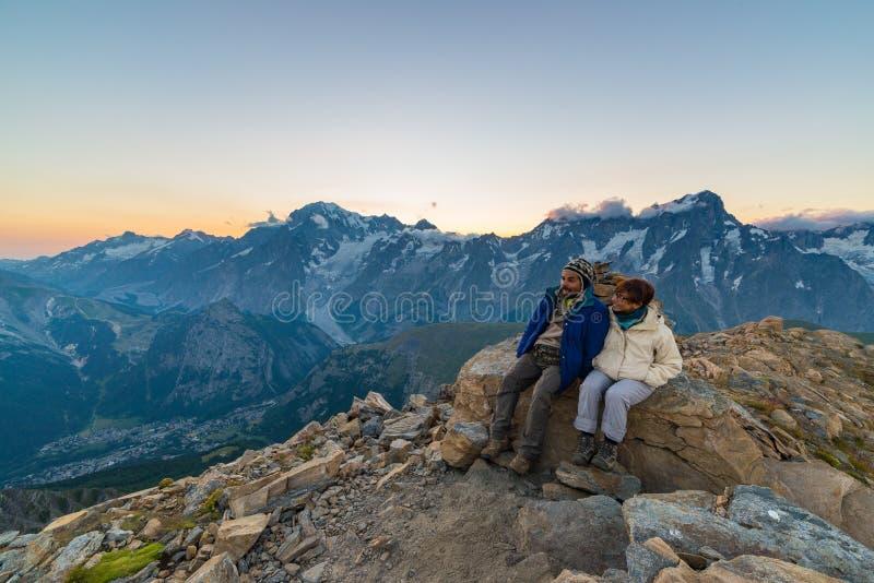 Paar van mensen die de zonsopgang over Mont Blanc-berg piek 4810 m bekijken Valle D ` Aosta, Italiaanse de zomeravonturen en trav stock afbeeldingen