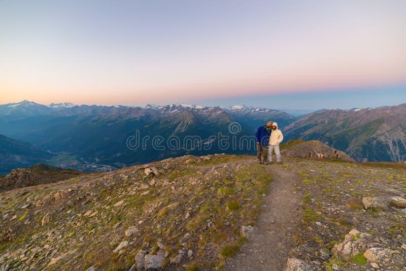 Paar van mensen die de zonsopgang over Mont Blanc-berg piek 4810 m bekijken Valle D ` Aosta, Italiaanse de zomeravonturen en trav royalty-vrije stock afbeelding