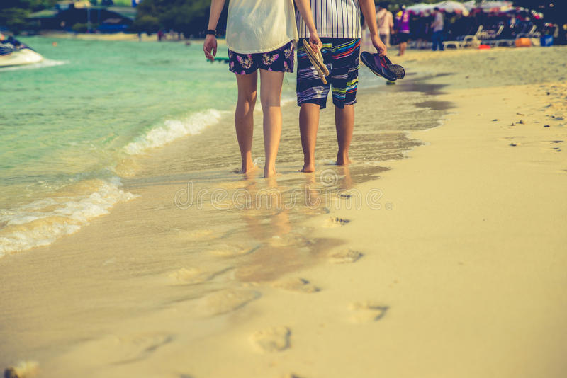 Paar van minnaars die op elk bij zonsopgang lopen - de Voet drukt het strand royalty-vrije stock foto