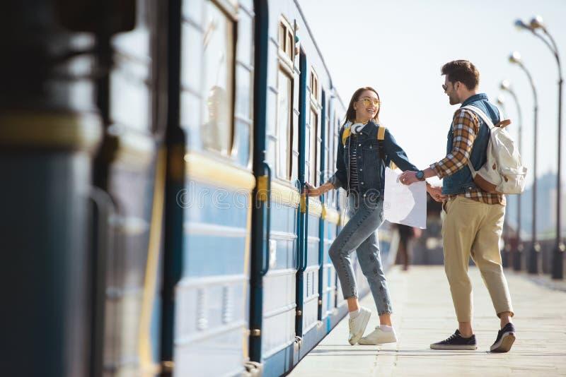 paar van modieuze toeristen met rugzakken en kaart die in trein bij openluchtmetro gaan royalty-vrije stock foto's