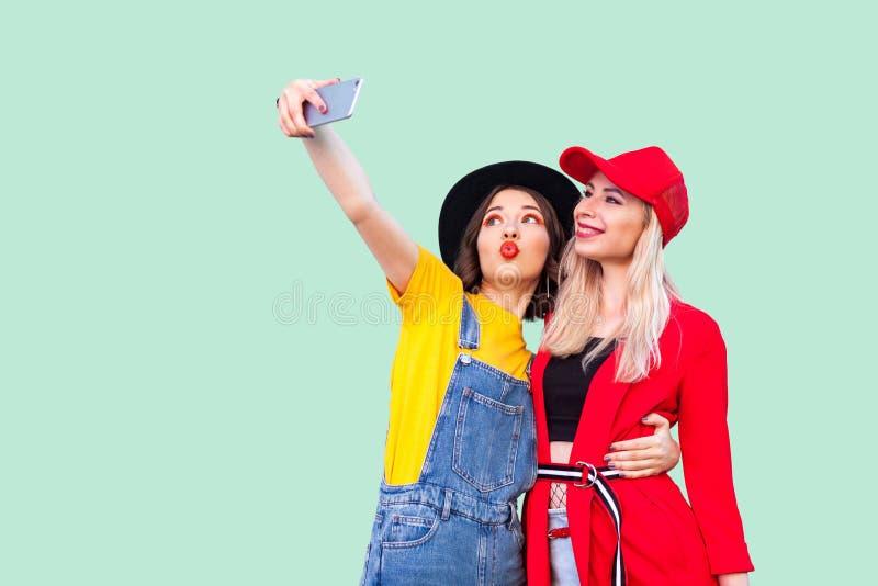 Paar van mooie stilysh hipster het best vrienden in modieuze met liefde koesteren, voor camera stellen en kleren die selfie maken stock afbeelding
