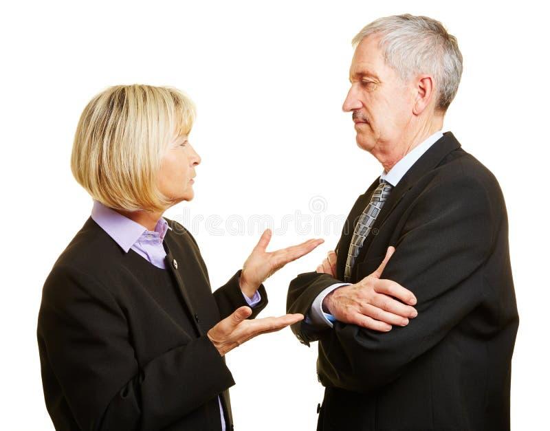 Paar van oudsten die en met elkaar spreken debatteren stock afbeeldingen