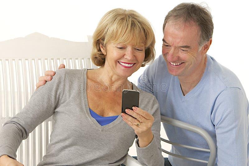 Paar van oudsten met mobiele gelukkig en telefoon die - glimlachen royalty-vrije stock afbeelding