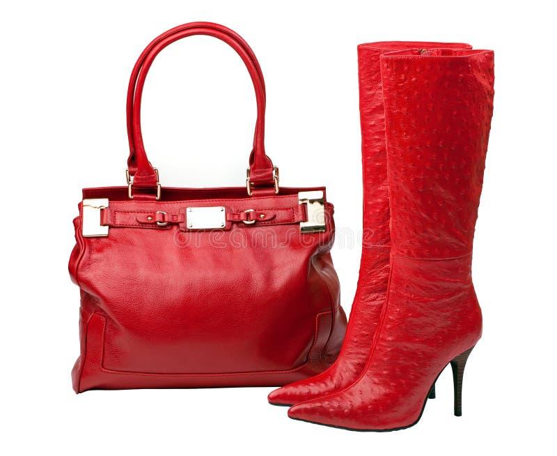 Paar van rode laarzen en vrouwelijke zak, met weg stock afbeelding