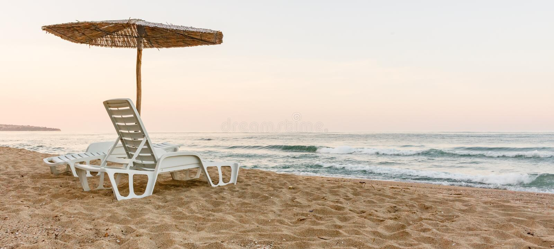 Paar van strand deckchairs op kust met paraplu voor overzees, zonsondergang, achtermening stock foto's