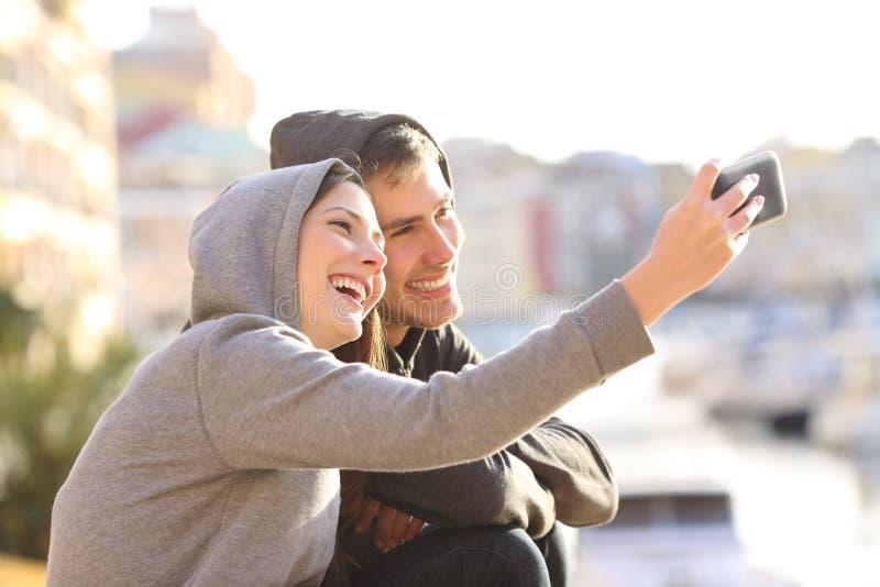 Paar van tienerjaren die een selfie in openlucht nemen royalty-vrije stock afbeeldingen