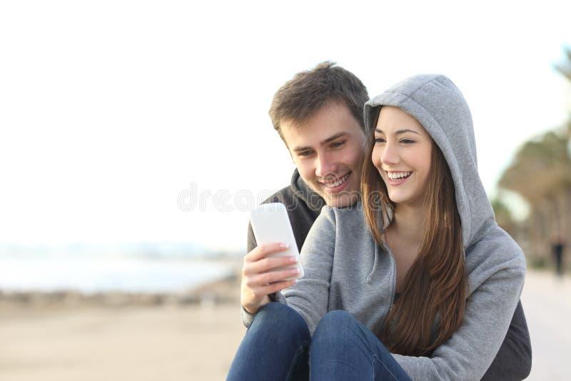 Paar van tieners die een slimme telefoon met behulp van royalty-vrije stock foto