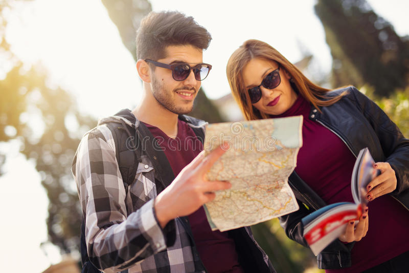 Paar van toeristen die de gids van de reiziger en een kaart bekijken royalty-vrije stock foto
