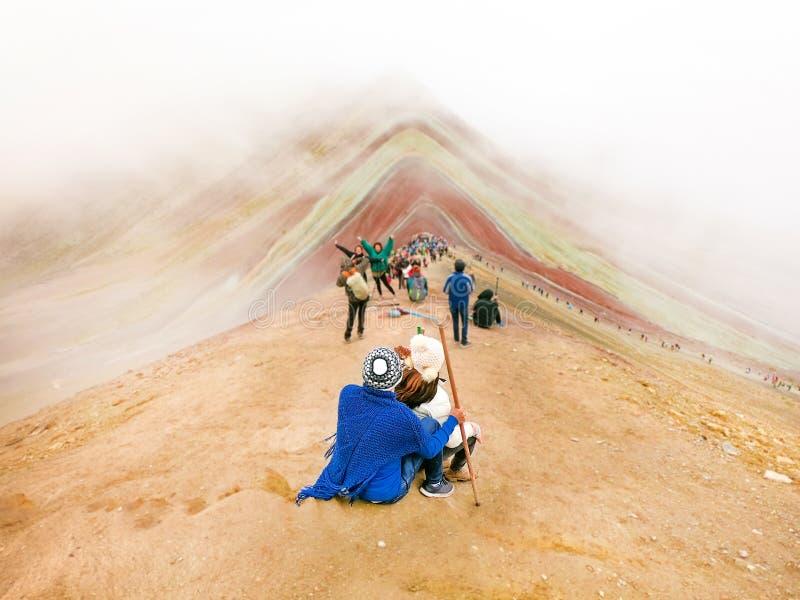 Paar van toeristen die en naar de Regenboogbergen zitten kijken, Cusco royalty-vrije stock foto