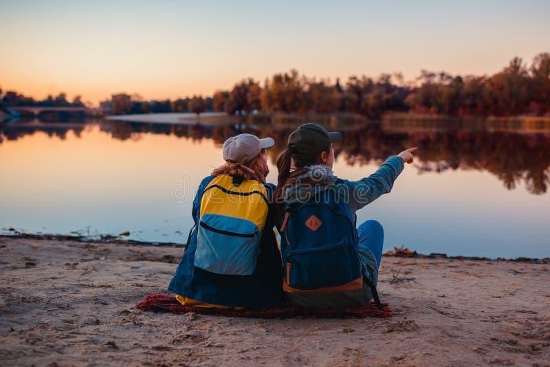 Paar van toeristen met rugzakken die door de bank van de de herfstrivier ontspannen Sportieve vrouwen die samen reizen Familietij royalty-vrije stock foto