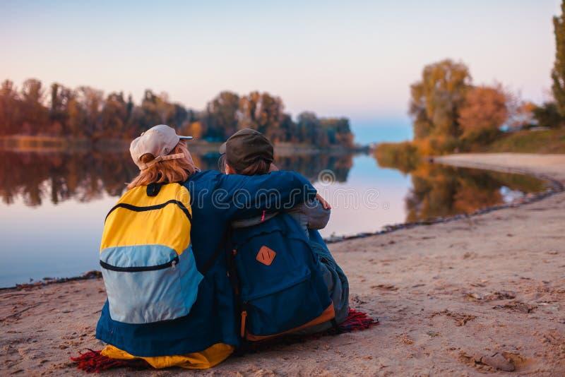 Paar van toeristen met rugzakken die door de bank van de de herfstrivier ontspannen Sportieve vrouwen die samen reizen Familietij stock afbeeldingen