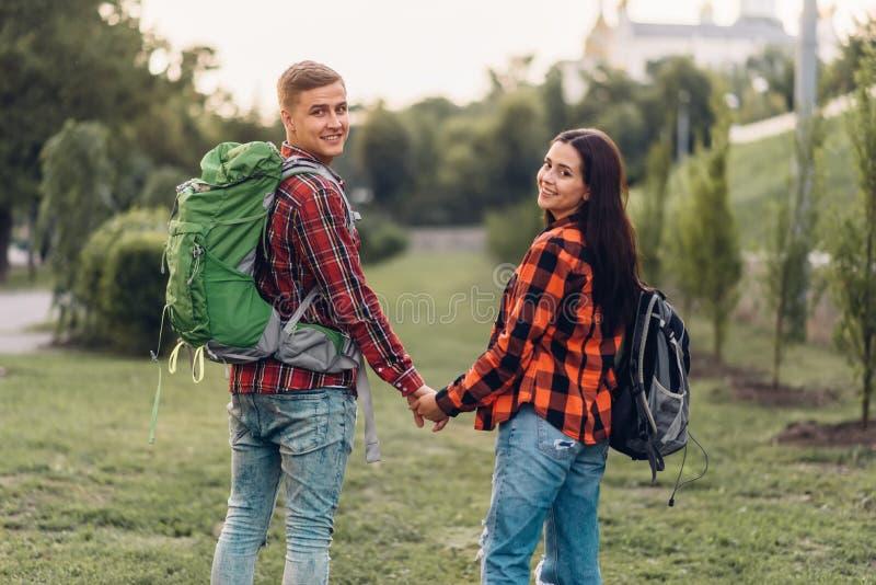 Paar van toeristen met rugzakken die handen houden stock afbeelding