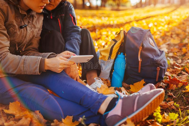Paar van toeristen met rugzakken die naar juiste manier zoeken die navigator in de herfst bosvrouwen gebruiken die rust hebben stock foto
