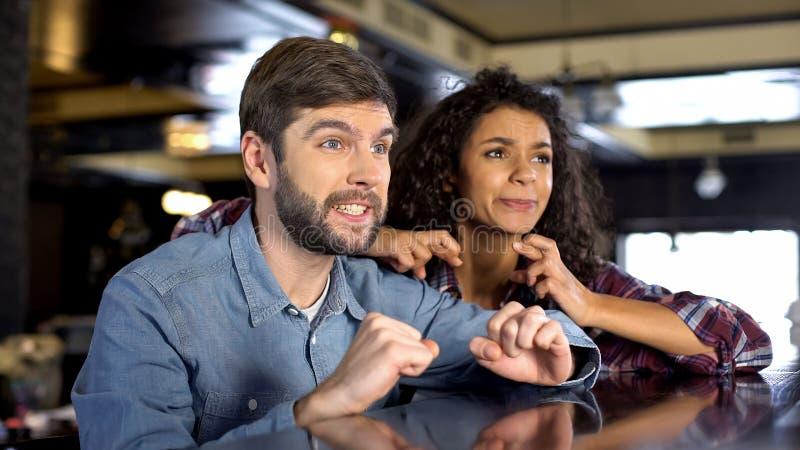 Paar van toeschouwers die vingers ondersteunend favoriet team van de concurrentie kruisen royalty-vrije stock foto's