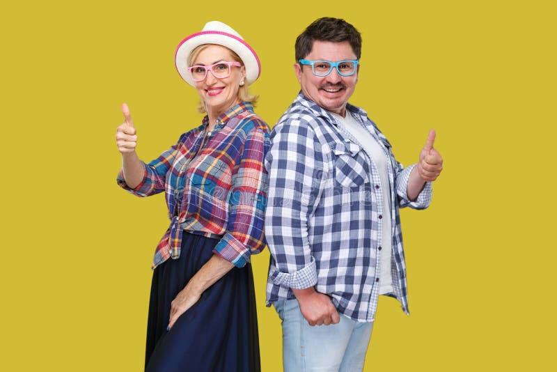Paar van vrienden, de volwassen mens en vrouw in zich het toevallige geruite overhemd rijtjes verenigen, tonend duimen, toothy gl stock afbeeldingen