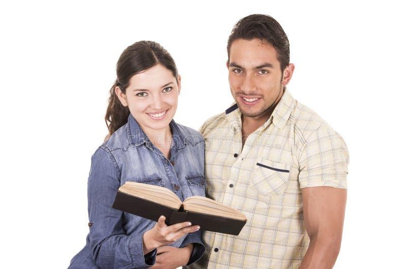 Paar van vrolijke gelukkige aantrekkelijke studenten die boek houden stock fotografie