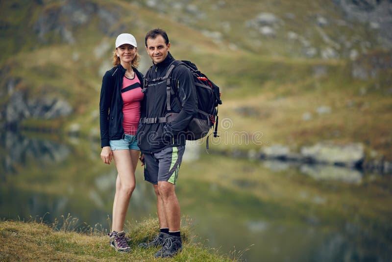 Paar van wandelaars dichtbij het meer stock afbeelding
