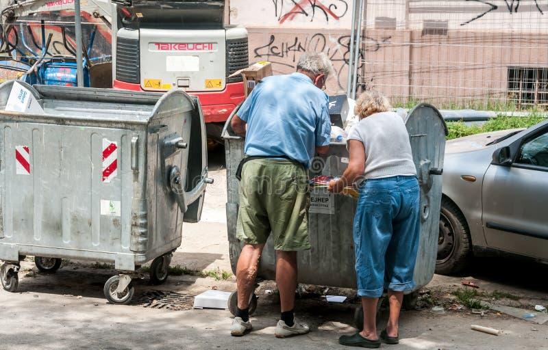 Paar von zwei älteren Leuten, die Sachen von der alten Metallmüllcontainerdose schauen und sammeln, soziales gibt Konzept heraus stockfotografie