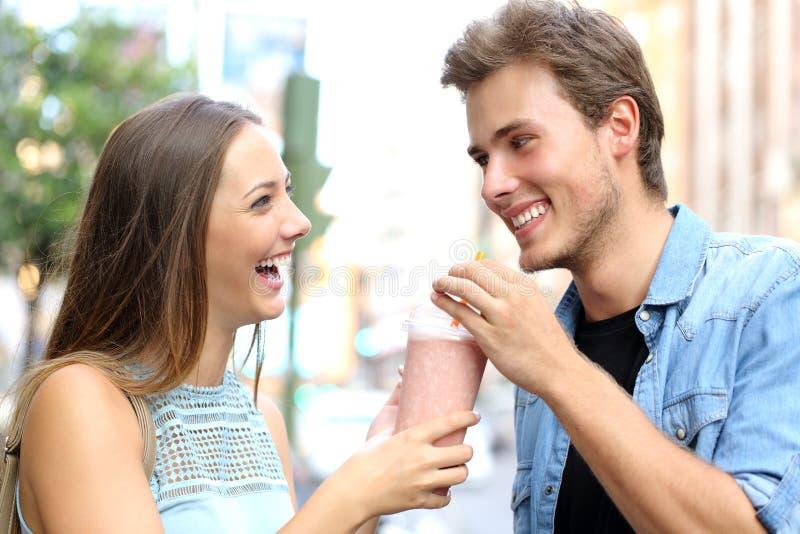 Paar of vrienden die een milkshake delen stock afbeeldingen
