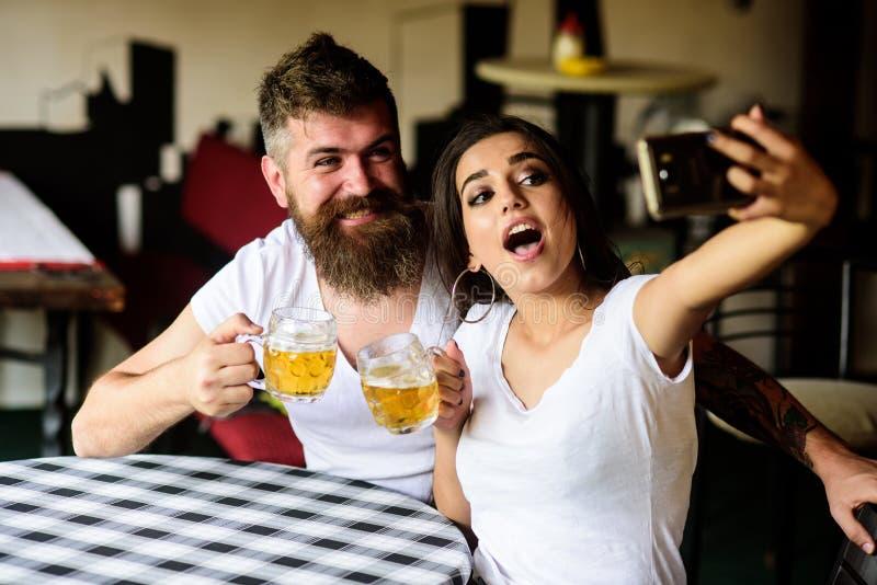 Paar vrolijk stemming het drinken bier in bar Het paar in liefde op datum drinkt bier Neem selfie foto om grote datum te herinner royalty-vrije stock afbeeldingen