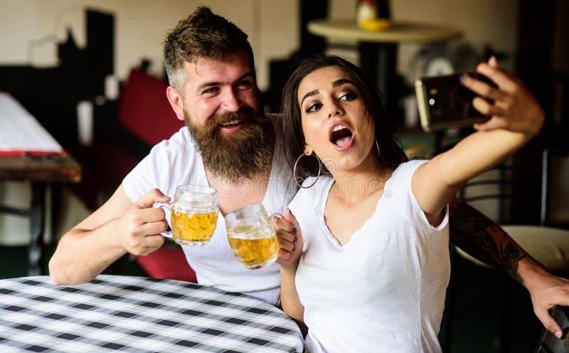 Paar vrolijk stemming het drinken bier in bar Mensen gebaard hipster en meisje met het hoogtepunt van het bierglas van ambachtbie royalty-vrije stock foto's