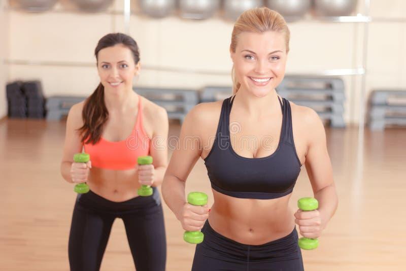 Paar vrouwen die gewichtengeschiktheid doen stock foto's
