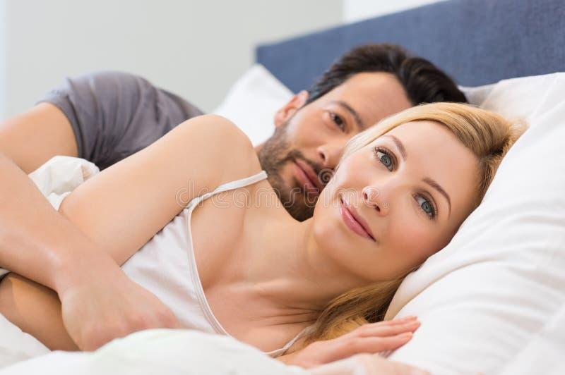 Paar wakker op bed royalty-vrije stock afbeelding