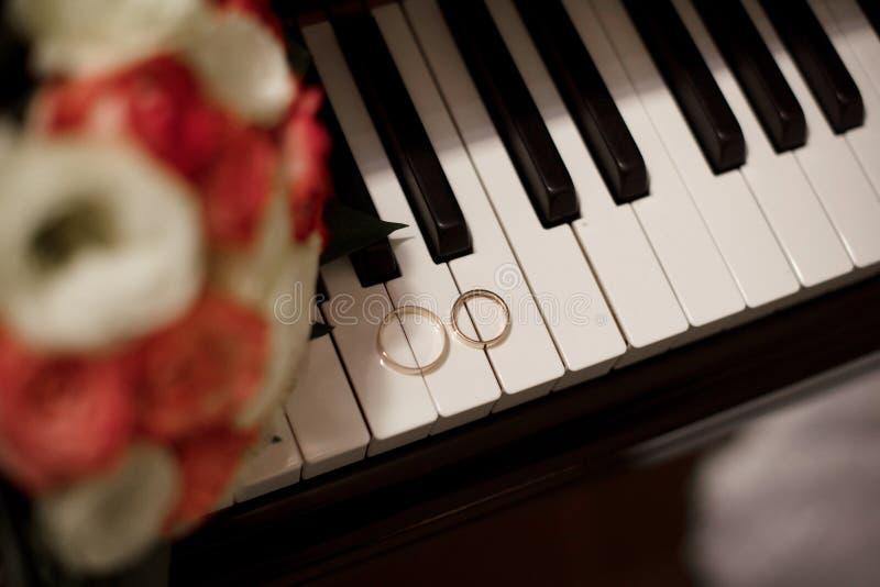 Paar witgoudtrouwringen met diamanten in de ring van vrouwen en steenoppervlakte in de ring van mannen Zilveren bruiloftringen op stock foto
