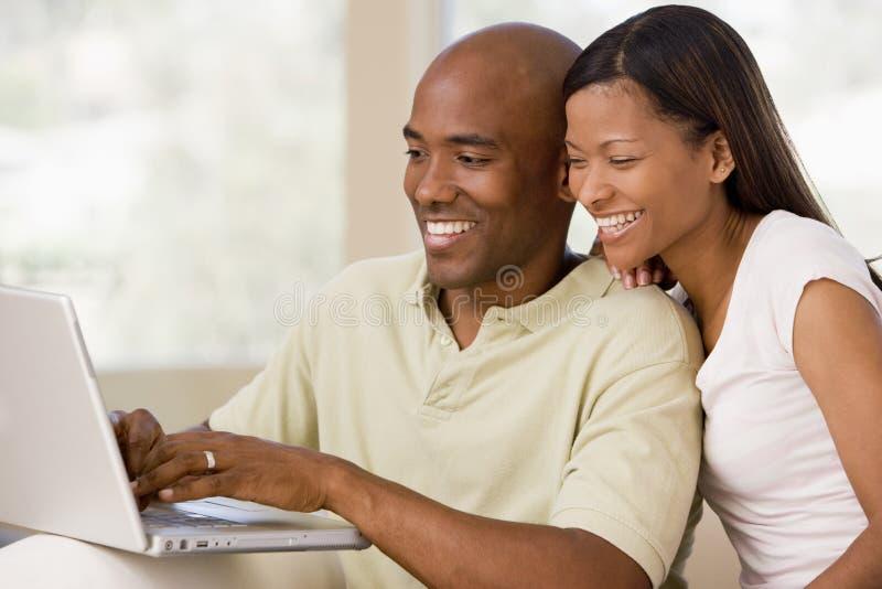 Paar in woonkamer die laptop met behulp van royalty-vrije stock foto's