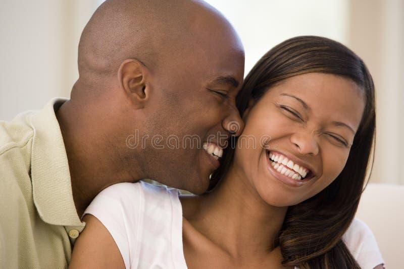 Paar in woonkamer het glimlachen stock afbeeldingen