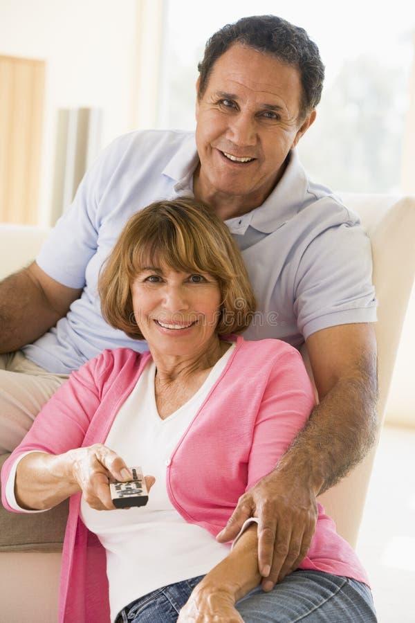Paar in woonkamer met afstandsbediening het glimlachen royalty-vrije stock fotografie