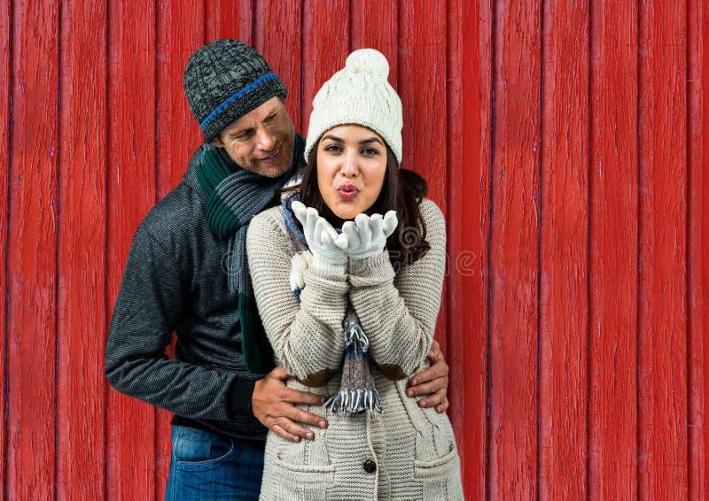 paar: zij die een kus verzenden en hij die zij met rode houten achtergrond kijken royalty-vrije stock foto