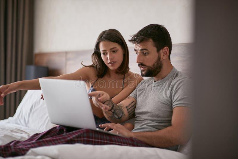 Paarbespreking in het bed met laptop en het surfen op Internet stock foto's