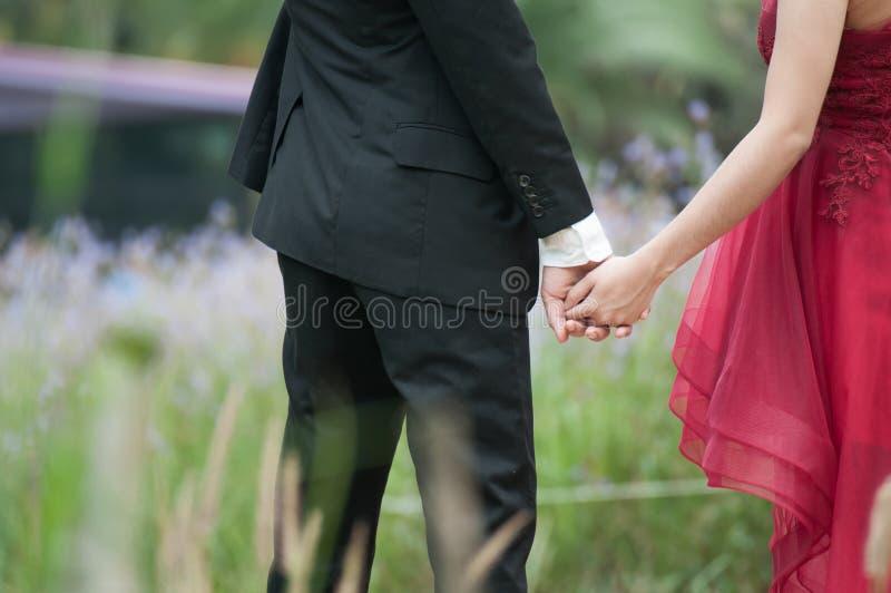 Paarbruid in huwelijkstoga en bruidegom in kostuum hand in hand stock afbeeldingen