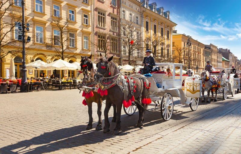 Paard getrokken vervoer met gidsen voor de St Mary Basiliek in Krakau, Polen stock afbeelding