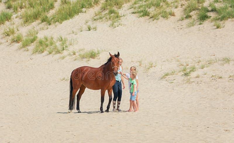 Paard met ruiter en twee meisjes op het strand van Noordzeetexel royalty-vrije stock afbeeldingen