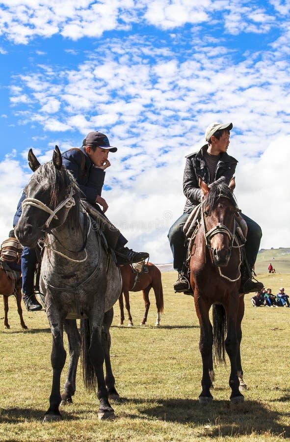 Paardrijden in Lied kul Meer in Kyrgyzstan stock foto