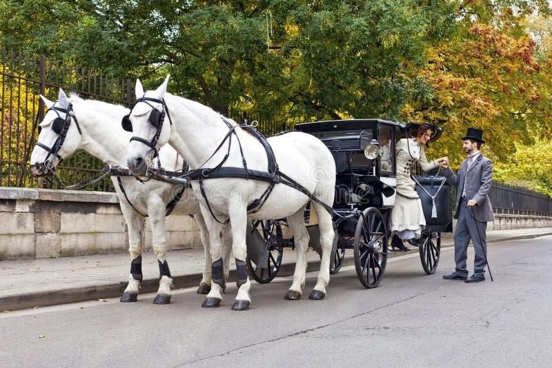 Paardvervoer met ouderwets gekleed paar stock afbeeldingen